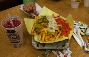 Chili Cheese Fries with tomatoes, pickles and onion at The Hat